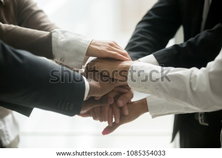 Diverse multiracial business team holding stacked pile of hands together promising help loyalty support, engaging in teambuilding, united at motivating training, coaching concept, close up view