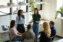Diverse multiracial businesspeople gather at briefing brainstorm discuss company business ideas together, multiethnic colleagues talk consider financial startup project at office meeting