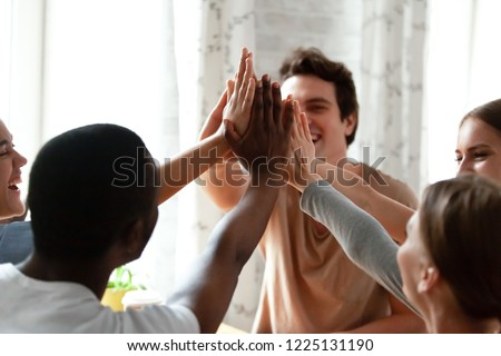 Diverse multiracial cheerful students giving high five greeting each other. Multi-ethnic millennial group of young people slapping palms sitting indoors. Gesture of celebration, friendship and unity