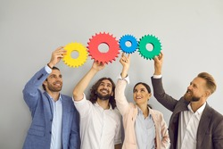 diverse multiracial colleagues isolated on grey background connect cog gear find business solution. Happy employees workers hold cogwheel engaged in teamwork. Brainstorming, creativity concept.