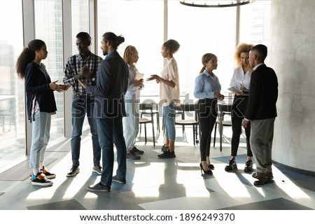Diverse multiracial colleagues talk in groups discuss ideas at casual team meeting in office. Focused multiethnic businesspeople speak brainstorm cooperate at workplace. Teamwork concept. Stockfoto ©