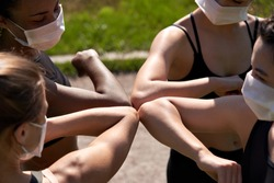 Diverse multiracial fit girls friends wear face masks give elbow bump. Sporty african, indian and caucasian young women group non-contact greeting together starting outdoor fitness training. Closeup.