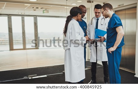 Diverse multiracial medical team consulting on a patient records standing in a foyer at a hospital grouped around a tablet computer