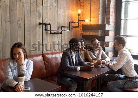 Shutterstock Diverse multiracial people hanging together in coffeehouse ignoring sad young girl sitting alone at cafe table, upset social outcast loner suffers from unfair attitude or discrimination among friends