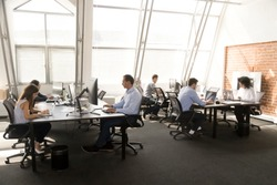 Diverse multiracial workers sitting at desk working in coworking space. Busy six businesspeople coworkers using computers typing chatting solving business matters in modern light contemporary office