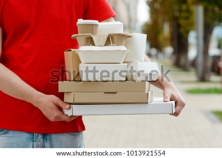 Diverse of paper containers for takeaway food. Delivery man is carrying pizza, Chinese noodles, burgers and coffee. #1013921554