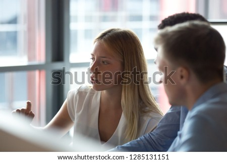 Diverse office workers sitting at desk looking at pc screen, focus on caucasian attractive skilled team leader woman share thoughts telling about online project or mentor explain computer software