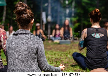 Diverse people enjoy spiritual gathering An open minded group of mixed individuals are seen sitting around a campsite in deep meditation seeking mindfulness and enlightenment. #1521574586