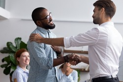 Diverse people gathered in meeting executive manager shake hands with black employee impressed by professionalism for leadership qualities creative solutions and efforts rewarding him for amazing work