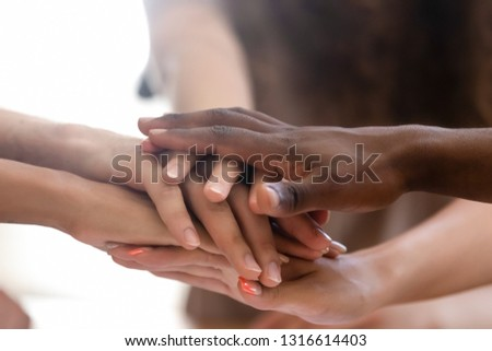 Diverse people group stacked joined hands in pile close up view, multiethnic team friends students together as racial unity concept, partnership coaching training, teambuilding, support in teamwork