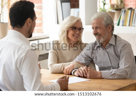 Diverse people sit at desk in office, male realtor make property offer for sale to elderly spouses old customers contract lie on table, buy new home, take bank loan or medical health insurance concept