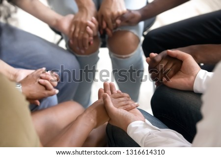 Diverse people sitting in circle holding hands at group therapy session, religious christian team pray together for recovery give psychological support, counseling training trust concept, close up