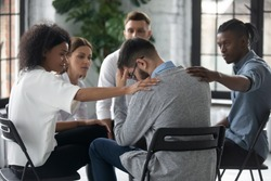 Diverse people supporting unhappy man at therapy session, touching shoulders, sitting in circle. Stressful businessman getting psychological help, trust and support, drug alcohol addiction treatment.