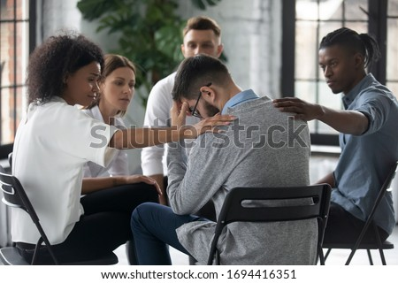 Diverse people supporting unhappy man at therapy session, touching shoulders, sitting in circle. Stressful businessman getting psychological help, trust and support, drug alcohol addiction treatment. Stock photo ©