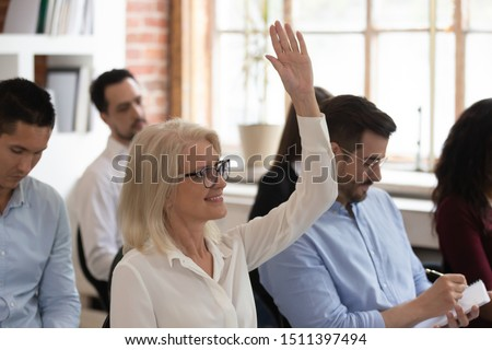 Diverse people takes part in conference or seminar sitting on chairs in office room, focus on middle-aged female raises hand to ask question active participant of training, corporate education concept