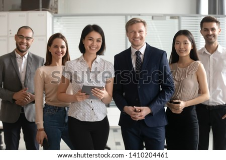 Diverse professional business leaders posing with multicultural workers in office, corporate coaches mentors stand together with employees group, happy staff people looking at camera, team portrait #1410204461