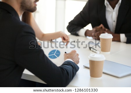 Diverse professional team sitting at desk analyzing statistics financial report during business meeting, closeup focus on chart diagram shown on paper. Concept of research, teamwork and brainstorm