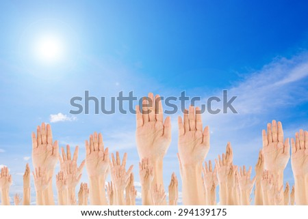 Diverse Raised Hands on sky background