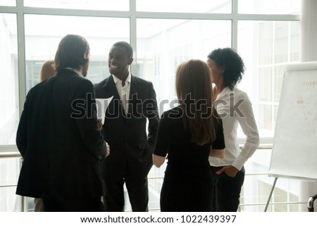 Diverse smiling businesspeople having conversation standing together at meeting, multiracial group talking to black business coach after training conference, executive team discuss work in office