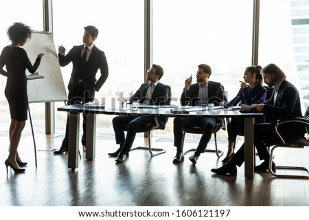 Diverse speakers or trainers present business financial project on flip chart to multiracial businesspeople at briefing, serious couches make whiteboard presentation at office meeting to employees
