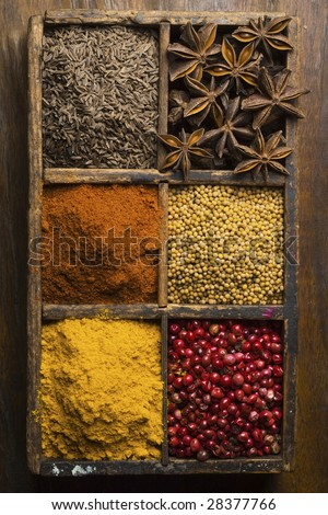 diverse spices in a wooden box (peppers, star anise, cummin, mustard seed)
