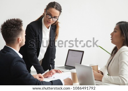 Diverse stressed subordinates scared of angry dissatisfied female boss scolding employees at team meeting, strict businesswoman leader showing authority reprimanding workers for bad work results