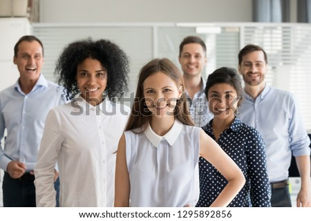 Diverse team headed by successful attractive leader woman standing together in a row indoors. Office workers caucasian indian and african nationality coworkers company staff posing looking at camera