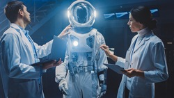 Diverse Team of Aerospace Engineers Design New Space Suit Adapted for Galaxy Exploration and Travel. Group of Scientists Wearing White Coats have Discussion, Use Computers. Constructing Astronaut Suit