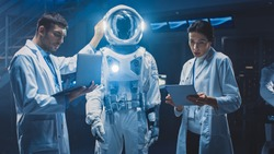 Diverse Team of Aerospace Scientists and Engineers Wearing White Coats have Discussion, Use Computers, Design New Space Suit Adapted for Galaxy Exploration and Travel. Constructing Astronaut Suit