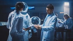 Diverse Team of Aerospace Scientists and Engineers Wearing White Coats have Discussion, Use Computers, Construct Astronaut Helmet for New Space Suit Adapted for Galaxy Exploration and Travel.