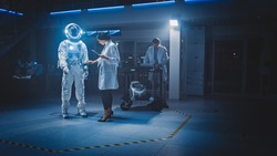 Diverse Team of Aerospace Scientists and Engineers Wearing White Coats Use Computers to Design New Space Suit Adapted for Galaxy Exploration and Travel. Constructing Astronaut Suit