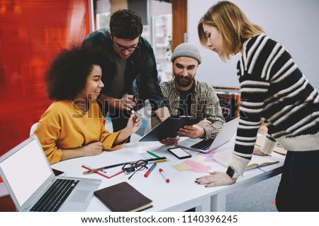 Diverse team of creative male and female designers in casual wear collaborating on development of project sitting at meeting table in office.Successful young people cooperating with each other
