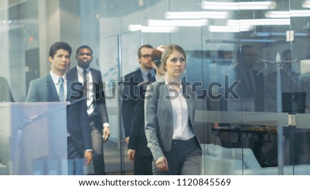 Diverse Team of Delegates/ Lawyers Led by Woman Confidently Marches Through the Corporate Building Hallway. Multicultural Crowd Of Resolute Business People in Stylish Marble and Glass Offices.