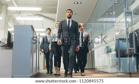 Diverse Team of Delegates/ Lawyers Resolutely Marching Through the Corporate Building Hallway. Multicultural Crowd Of Businessmen and Businesswomen in Action.
