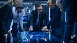 Diverse Team of Government Intelligence Agents Standing Around Digital Touch Screen Table and Tracking Suspect. FBI Agents Using Satellite Surveillance in the Dark Monitoring Room.