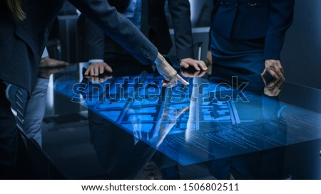 Diverse Team of Government Intelligence Agents Standing Around Digital Touch Screen Table and Satellite Tracking Suspect, Pointing at Display. Big Dark Surveillance Room.
