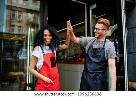 Diverse team of positive professional barista and experienced waiter in aprons giving five each other standing outdoors near own coffee shop.Cheerful young man and woman developing own cafe business