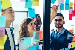 Diverse team of positive young people laughing while working together during brainstorming and standing behind glass wall with sticky colorful papers.Cheerful students learning words from stickers