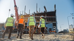 Diverse Team of Specialists Inspect Commercial, Industrial Building Construction Site. Real Estate Project with Civil Engineer, Investor and Businesswoman. In the Background Skyscraper Formwork Frames