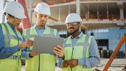 Diverse Team of Specialists Use Laptop on Construction Site. Real Estate Building Project with Engineer Investor and Businesswoman Checking Area, working on Civil Engineering, Discussing Strategy Plan