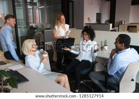 Diverse teammate enjoy break during working day drinking coffee in carton cups chatting feeling good. African joyful woman telling funny story from life to colleagues while resting in coworking office #1285127914