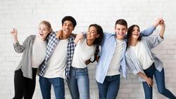 Diverse teens embracing and posing over white brick wall, looking at camera