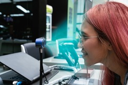 Diverse woman using biometric scanner to confirm identity and pay for retail shopping transaction - Young girl using facial recognition ID at bank - Cyber security, verification and cashless concept