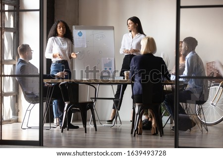 Diverse women startupper mixed-race and european ethnicity make perform presentation for investors during meeting at office boardroom, staff listening coaches attending at educational training concept
