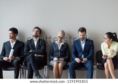 Diverse work candidates sitting in queue in office expecting their turn for interview, multiethnic job applicants waiting in corridor preparing for recruiting process. Employment, hiring, HR concept