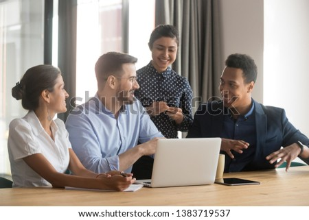 Diverse work team sit at office desk talking brainstorming on project strategy, smiling multiethnic employees discuss share ideas cooperating using laptop at office meeting. Collaboration concept
