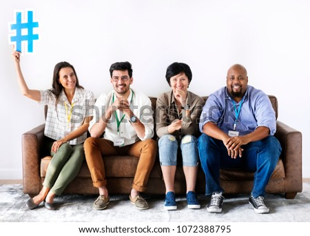 Diverse workers sitting together woman holding hashtag icon