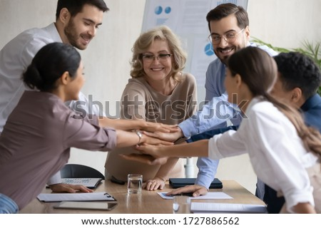Diverse workers with mature mentor, putting hands together, showing support and unity after successful presentation at company meeting. Happy female teacher with colleagues in team building activity.