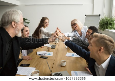 Diverse young and senior business people giving high five building successful team at meeting, motivated multiracial group of different age uniting celebrating win promising support help in teamwork