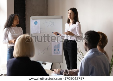 Diverse young female speakers present business financial project on whiteboard for employees at meeting, focused woman couch make flip chart presentation for multicultural colleagues at briefing
